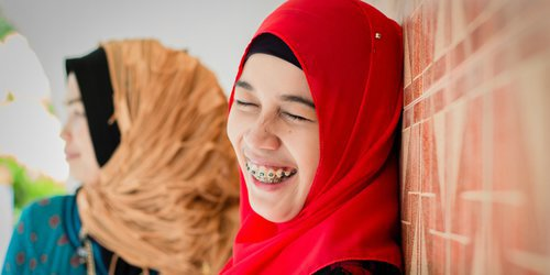 the veiled woman is leaning and smiling