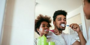 Dad is teaching his frivolous son to brush his teeth