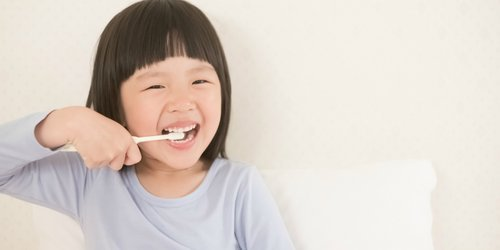 Slanted little girl is brushing teeth
