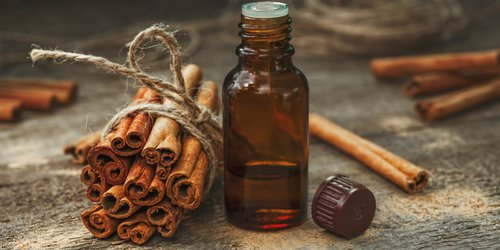 a bunch of cinnamons and a bottle of its extraction