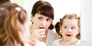 Mother persuade her daughter to brush her teeth to make good habit