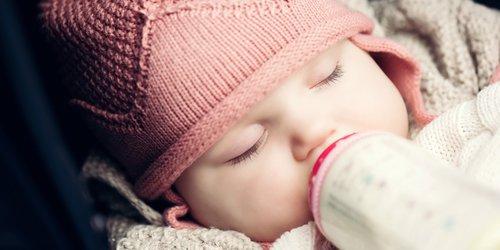sleepy baby drinking milk