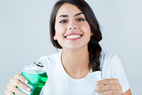 a woman take a sip of mouthwash before going to bed