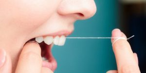 woman using dental floss to clean her teeth