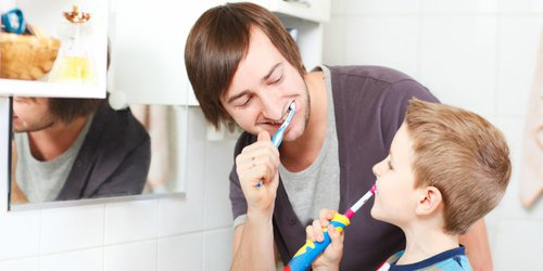 a kid trying new toothbrush that is chose by his father
