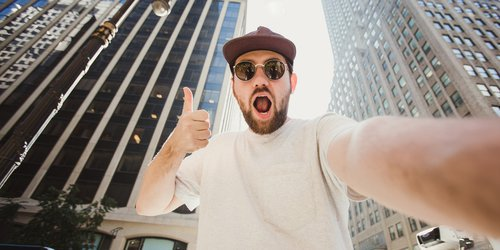 A man taking a selfie between buildings confidently opening his mouth widely