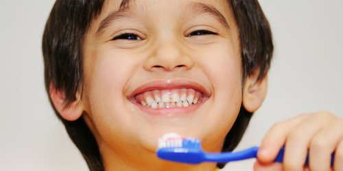 little boy is brushing his teeth while smiling
