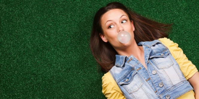 Woman lying on the ground chewing bubble gum