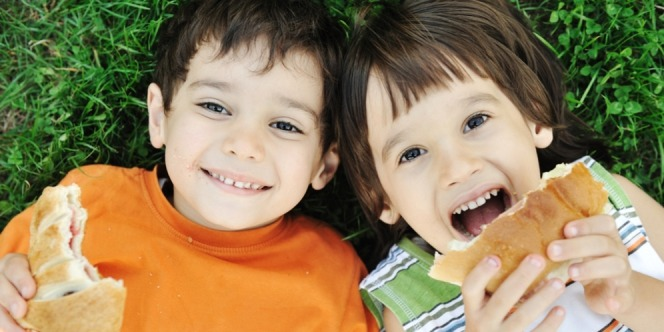 Two happy kids are eating a wheat bread for snack