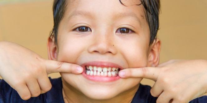 Kid showing off his healthy teeth grow