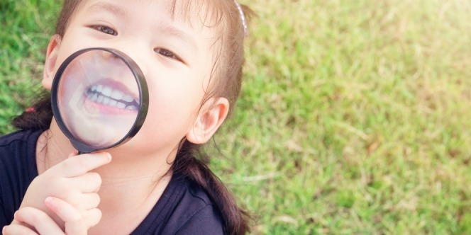 a small child holding a magnifying glass